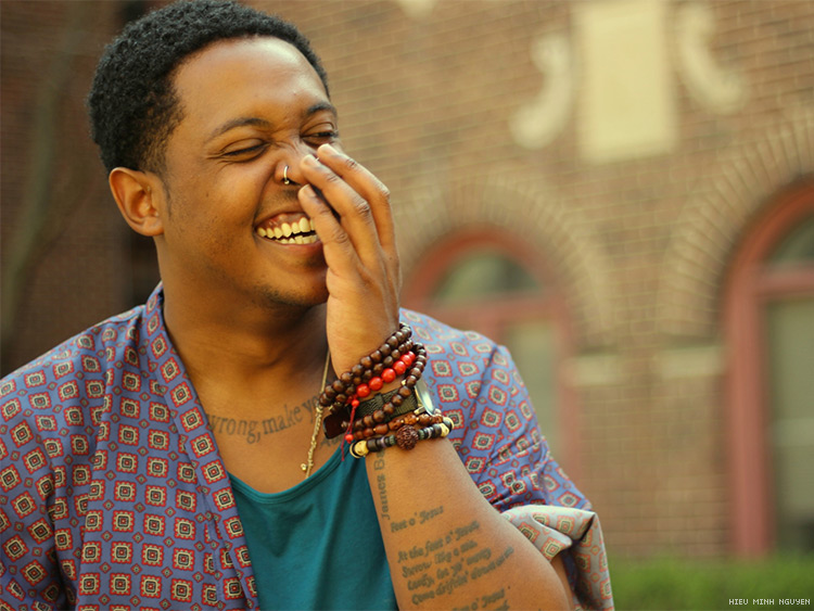 Headshot of Danez Smith, a black queer male poet, laughing and looking toward side of frame