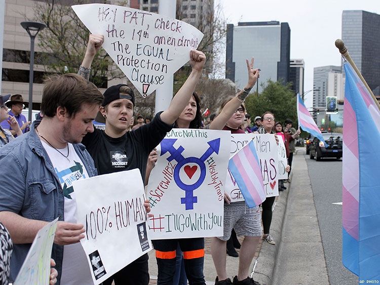 Demonstrators protesting passage of legislation limiting bathroom access for transgender people stand in front of the Charlotte-Mecklenburg Government Center in Charlotte.