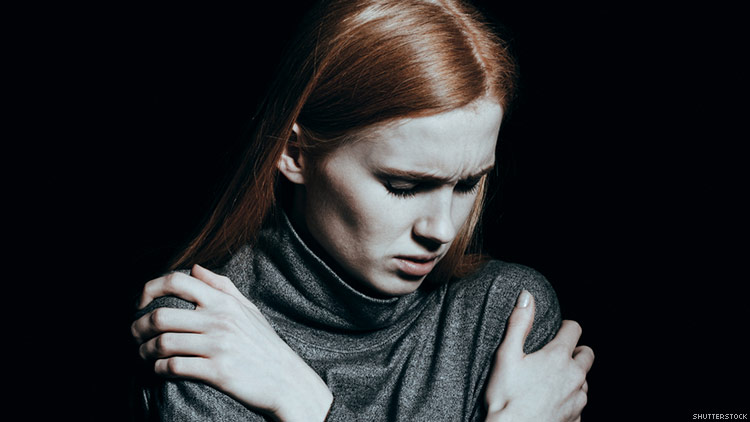 An upset looking woman, holding herself.