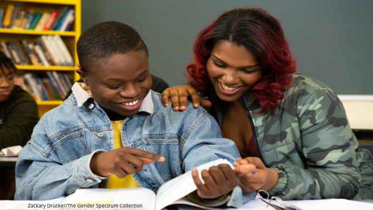two trans students reading book, one feminine, one masculine, both African-American
