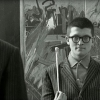 Hockney, standing in front of We Two Boys Together Clinging, 1961