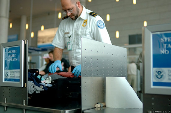 A TSA agent checks luggage