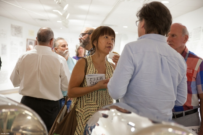 Yiwen Chow holds onto her program for The Gay Rub exhibition and talks with other attendees.