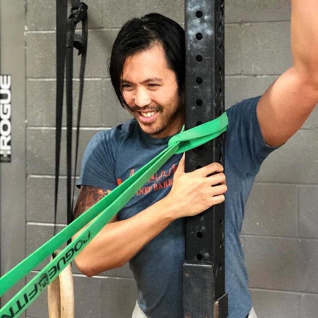 Stephan Wang stretching before a workout at his box, CrossFit Defined, in Chicago Illinois.