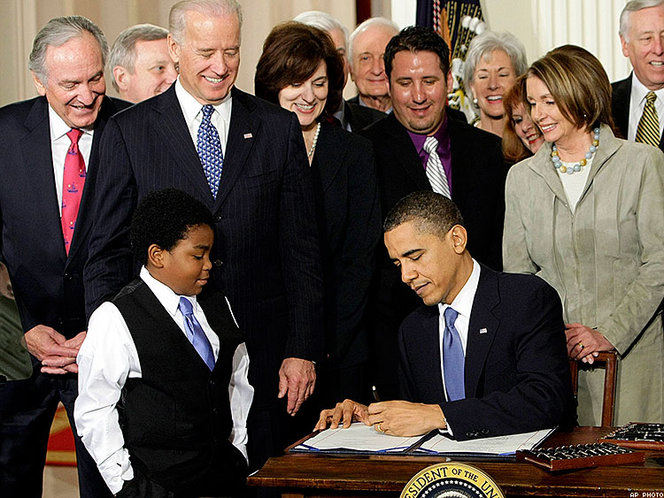 President Barack Obama signs the Affordable Care Act in the East Room of the White House on March 23, 2010 as Marcelas Owens watches.