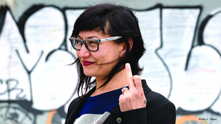 Photo of Asian-American cartoonist MariNaomi raising a middle figner