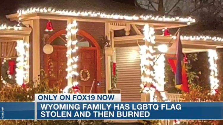 The front porch of a home with christmas lights and a pride flag