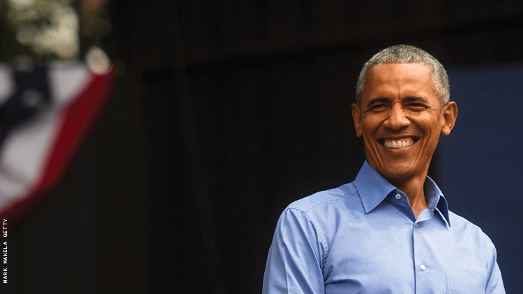 president obama, a black man with gray hair, is smiling near a flag