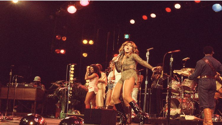 Tina Turner, a young fit Black woman in a dress, on stage in the 1970s