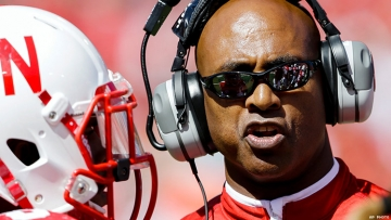 Ron Brown, football coach, wears sunglasses and headphones. A football player, whose face is obscured by a white helmet, stands to his right.