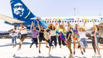 LGBTQ travel influencers in front of Alaska Airlines Pride plane