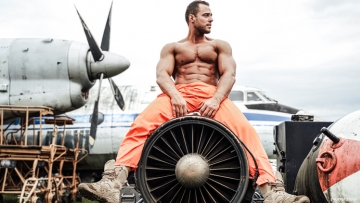 Shirtless man straddles airplane engine