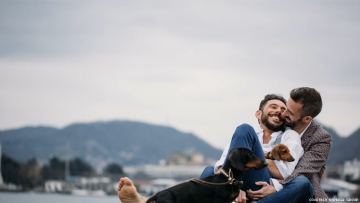 Gay male couple with two dogs relax in front of a lake and mountains
