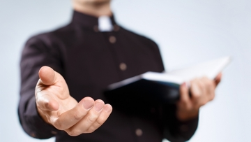 priest reaching out his hand