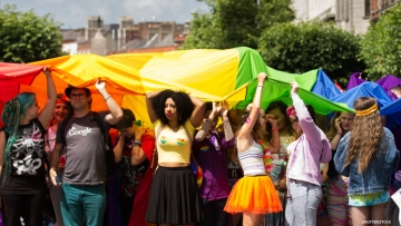 Pride crowd holding up a rainbow flag