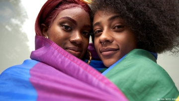 Two Black Lesbians wrapped in a Pride Flag
