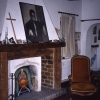 The upstairs living room with Baldwin's portrait, a cross, and mantelpiece collage.