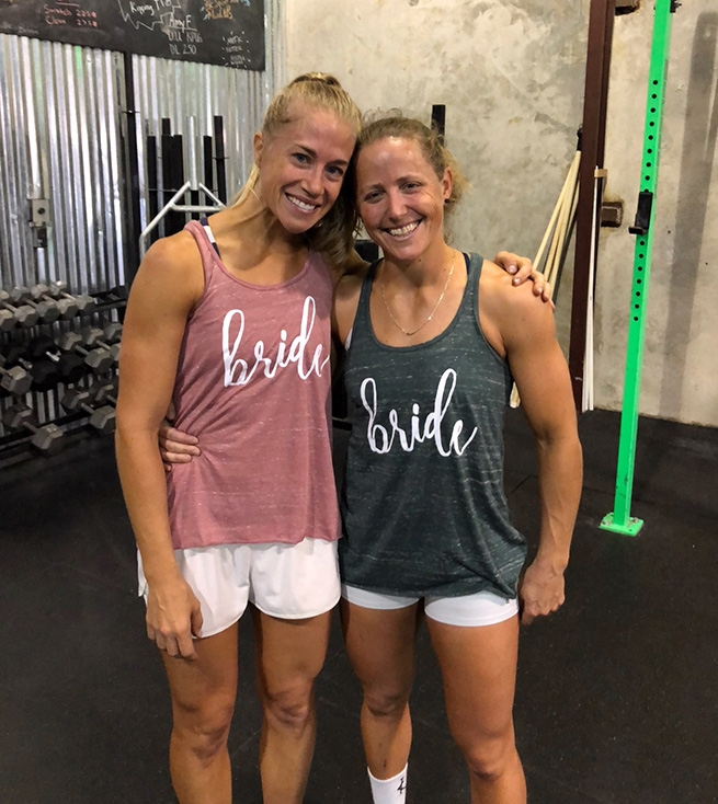 Michelle Kinney (right) — 2014's 12th Fittest Woman in the World — with her wife Lauren Hinrichs (left) during their 'wedding day workout' in 2018