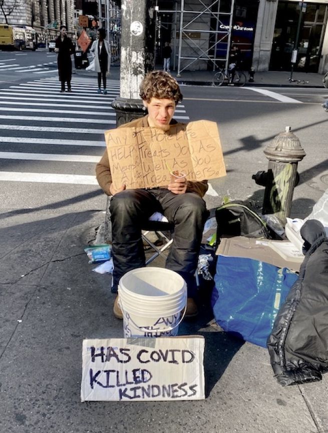 homeless person living in New York City looks at the camera