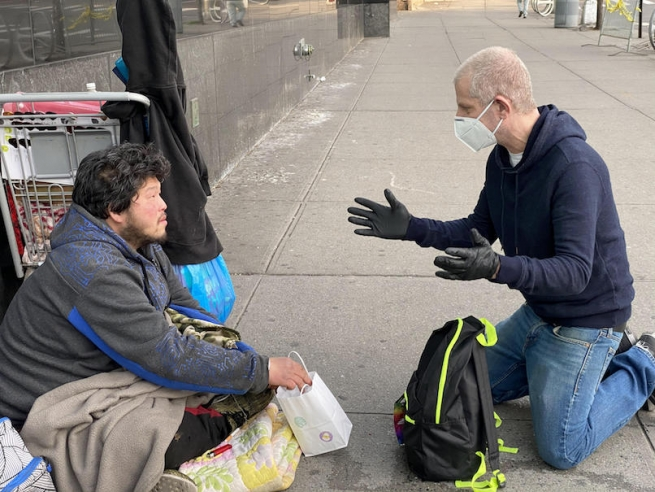 Jeffrey helping someone living on the streets of New York City