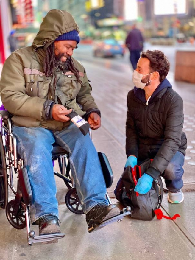 Jayson helping someone who is living on the street in New York City