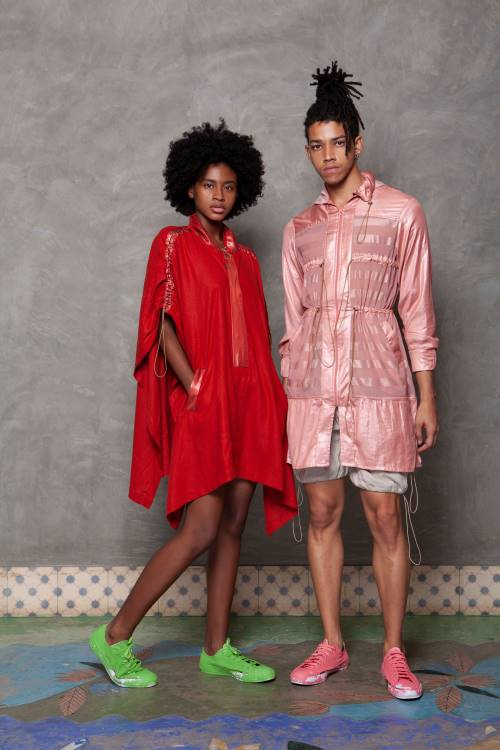 woman wearing a red cape-like jacket, man wearing pink jacket both by WeDu by Coreon Du